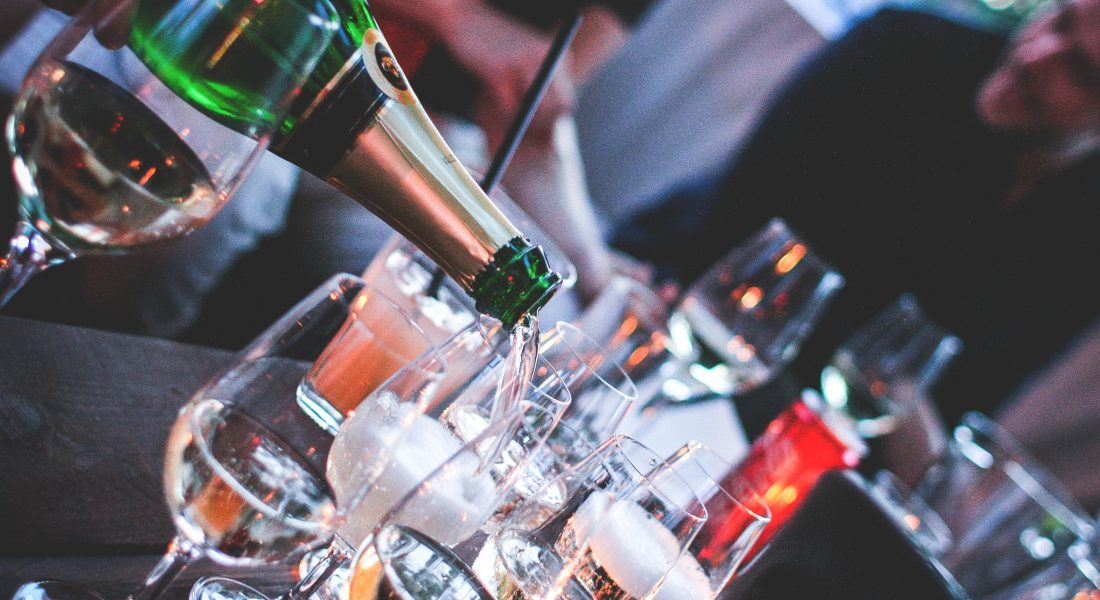 photo of someone pouring champagne at an angle into a flute on a crowded table