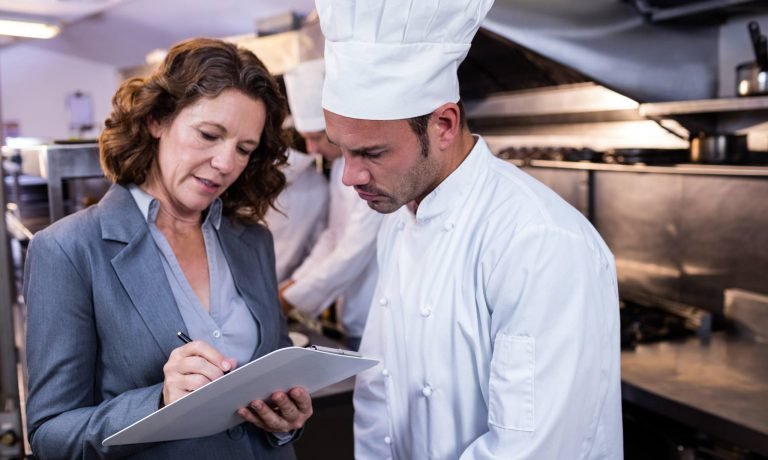 restaurant manager and chef looking at licenses