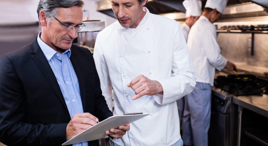 Male restaurant manager writing on clipboard conducting staff training