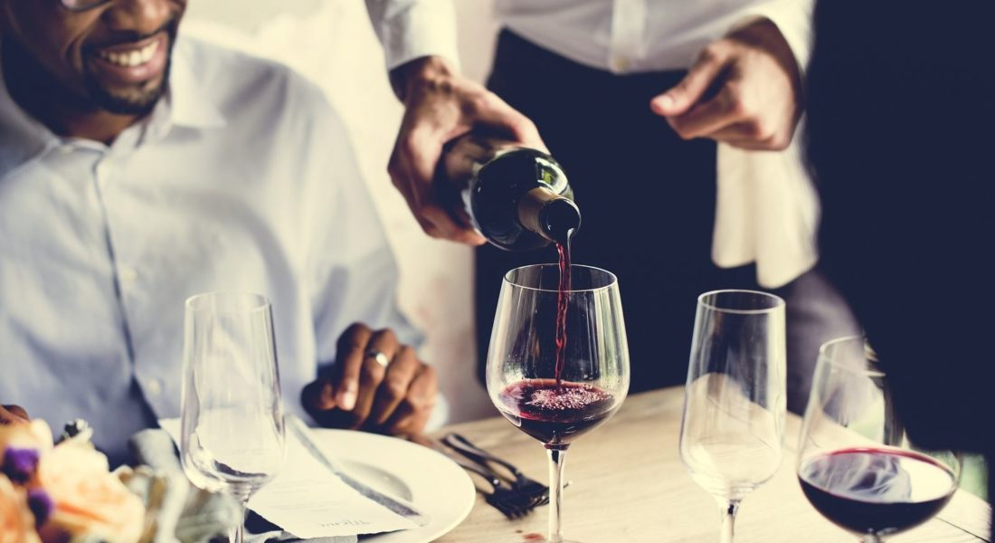 Restaurant Staff Poring Serving Red Wine to Customers