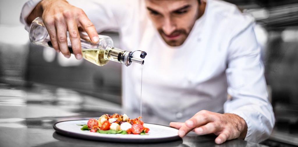 restaurant chef pouring oil on food