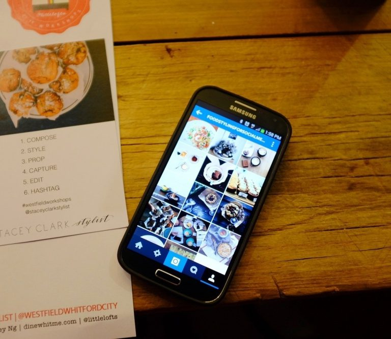 an iphone on a table with a restaurant menu beside it