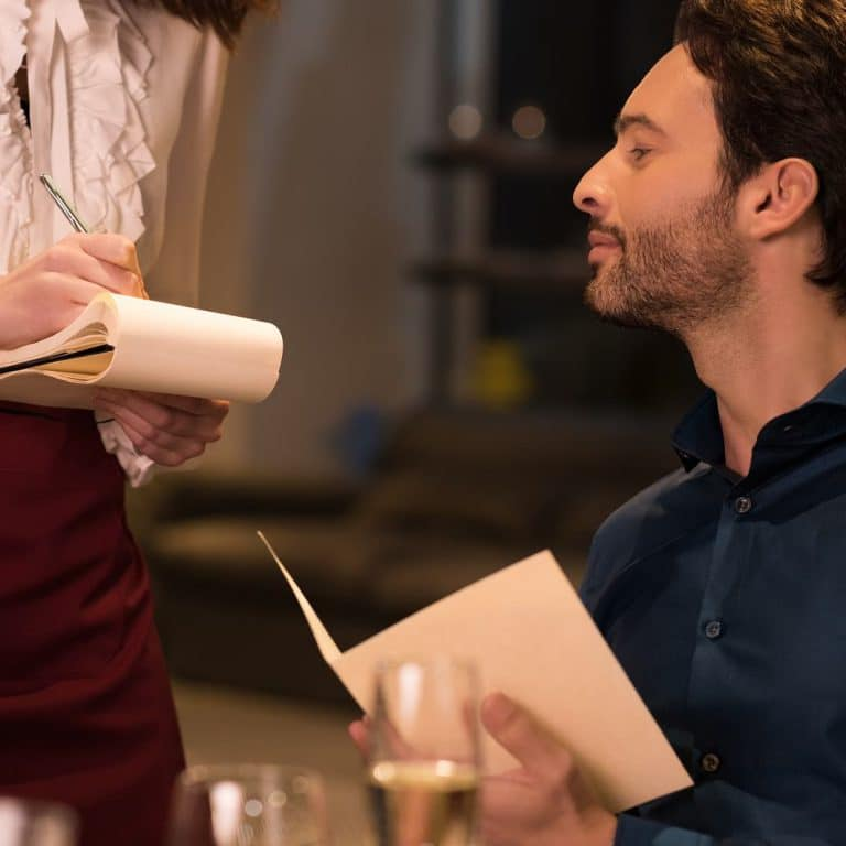 Young man ordering food in a restaurant. Handsome man checking his order written by waitress. Young waitress offering tasty dishes options to smiling guests. Waitress writing a order.
