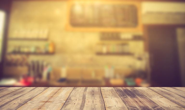Wood Table Top On Blur Background Of Coffee Shop (or Restaurant)